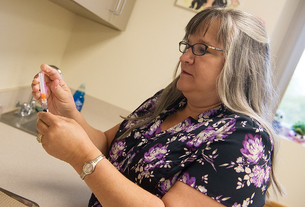 Globe/Roger Nomer<br /> Cynthia Burnham, medical services coordinator for the Joplin Department of Health, prepares a flu vaccine on Wednesday at the health department.