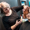 Globe/Roger Nomer<br /> Catlyn Pink gives a purple hair extension to Juanita Taylor, Carl Junction, on Tuesday at Salon 529 as part of Domestic Violence Awareness Month.