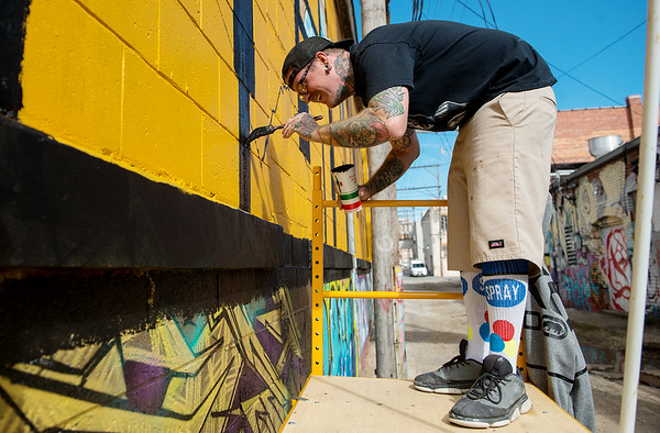 Derek Wieberg works on a mural in the alley west of Sixth Street in downtown Joplin on Thursday.<br /> Globe | Roger Nomer
