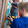 Jaden Glaze, an eighth grader at Carthage Junior High, helps hang a mural on Tuesday in Carthage.<br /> Globe | Roger Nomer