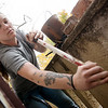 Jessie Williams cleans a balcony to prevent moisture runoff at a house on Moffet Street in Joplin on Tuesday.<br /> Globe | Roger Nomer