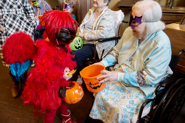 Everleigh Burpo, pre-kindergarten student at St. Mary's Elementary, gets a Halloween treat from Billie Ginn while visiting the Communities of Wildwood on Thursday. St. Mary's students traveled on a hayride escorted by a firetruck to the home.<br /> Globe   Roger Nomer