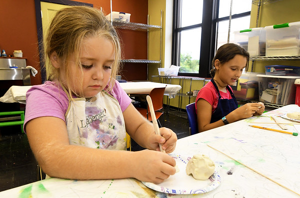 From the left: Abby Hicks, 7 and Charli Rainbolt, 9, create low relief scultures of seasonal ornaments using air-dry clay on Tuesday afternoon during Creation Station at the Spiva Center for the Arts.<br /> Globe | Laurie Sisk