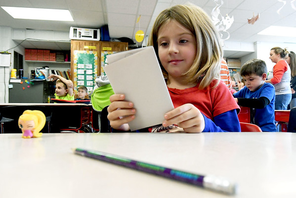 Lillian Stinebaugh, 5, reviews a book she created in Susan Wilson's kindergarten class on Friday at Granby Elementary. The district is reviewing the success of their four-day school week after two years of implementation.<br /> Globe | Laurie Sisk