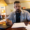 Michael Millman looks over paperwork related to his son's case at his home in Bronaugh on Sept. 20.<br /> Globe | Roger Nomer