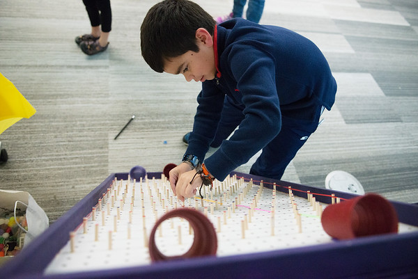 Samuel Herrera, 8, Joplin, works with a peg board during the Creative Learning Alliance's community forum on a children's museum on Tuesday at the Joplin Public Library.<br /> Globe | Roger Nomer