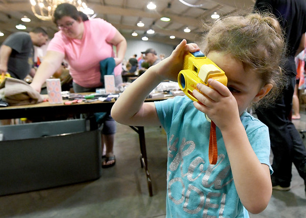 Three-year-old shutterbug Josie Bowman, of Vinita, checks out a toy camera she found at Joplin's Biggest Indoor Yard Sale on Saturday at Jack Lawton Webb Convention Center. The event was sponsored by The Joplin Globe.<br /> Globe | Laurie Sisk