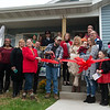Seth Hurtt cuts the ribbon to dedicate his family's new Habitat house on Wednesday.<br /> Globe | Roger Nomer