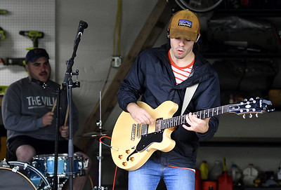 "Members of the band ""Trey"" entertain visitors from inside a garage during Porch Fest on Saturday in the North Heights Neighborhood. Globe 