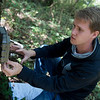 Caleb Durbin, a Pittsburg State University junior from Chanute, checks a wildlife camera on Friday near Pittburg.<br /> Globe | Roger Nomer