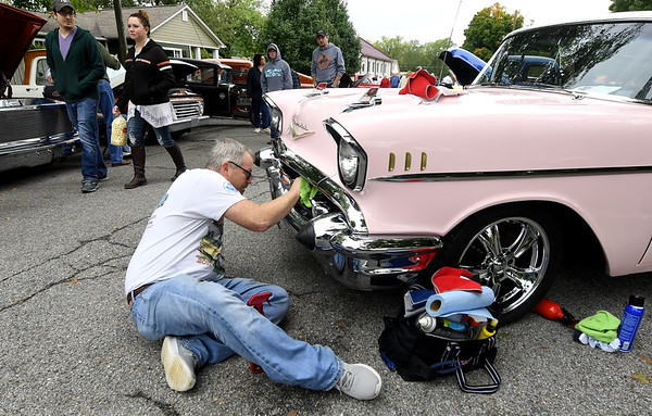 Justin Gilstrap, of Joplin, spruces up the fender of a 1957 Bel Air Nomad 2-door wagon owned by his wife, Catrina Gilstrap, on Saturday at the Decades of Wheels Grand Opening Weekend Car Show on Saturday in Baxter Springs. The weekend featured inflatable kids games, live music and more in downtown Baxter Springs.<br /> Globe | Laurie Sisk