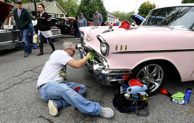 Justin Gilstrap, of Joplin, spruces up the fender of a 1957 Bel Air Nomad 2-door wagon owned by his wife, Catrina Gilstrap, on Saturday at the Decades of Wheels Grand Opening Weekend Car Show on Saturday in Baxter Springs. The weekend featured inflatable kids games, live music and more in downtown Baxter Springs. Globe | Laurie Sisk