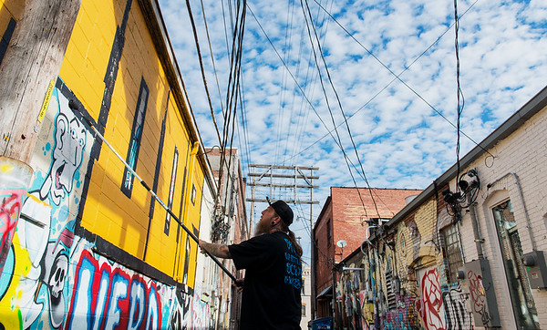 Darryl Becker works on a mural in the alley west of Sixth Street in downtown Joplin on Thursday.<br /> Globe | Roger Nomer