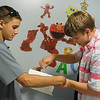 Lucas Millman, 14, helps his brother Michael Millman Jr., also known as Little Michael, decorate his room at Heartspring in Wichita, Kan., during a visit on June 8.<br /> Globe | Roger Nomer
