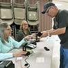 From the left: Election officials Frances Tewell and Joyce Kovacic staff the check-in table as Don Noland pulls his license from his wallet during early voting for the 2018 midterm election at the Homer Cole Community Center on Tuesday in Pittsburg. Election officials reported heavy turnout for early voting at the site.<br /> Gobe | Laurie SIsk