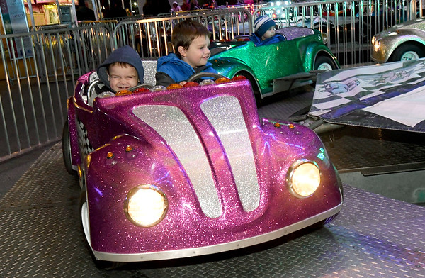 From the left: Cousins Roddy Roth, 2 and Rowan Roth, 3, enjoy one of the Pride Amusements kiddie rides on Wednesday night at the Maple Leaf Festival Carnival in Carthage. The carnival continues through Saturday night at the Fair Acres Complex.<br /> Globe | Laurie Sisk
