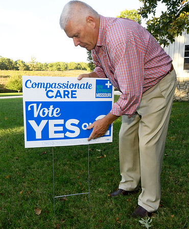 Retired cardiologist Paul Callicoat posts a yard sign on Wednesday at his Seneca home. Callicoat has been active in endorsing Proposition 2 for the legalization of medical marijuana.<br /> Globe | Laurie Sisk