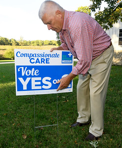 Retired cardiologist Paul Callicoat posts a yard sign on Wednesday at his Seneca home. Callicoat has been active in endorsing Proposition 2 for the legalization of medical marijuana. Globe | Laurie Sisk