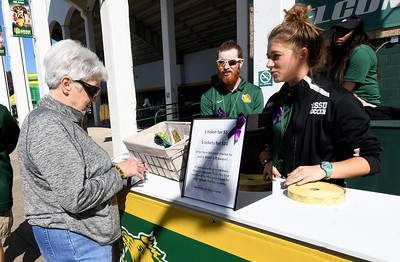 Fom the left: Kay Hollis donates money for a chance to win a MSSU gift basket as MSSU marketing inten Alex Gladbach and MSSU soccer players Anissa Williams and Ronise Miller staff a table to raise money for The Darin Moore Athletic Training Endowment Fund on Saturday at Fred G. Hughes Stadium. All profits from concessions and $2 off each ticket sold to the game also were contributed to the endowment. Moore, former head athletic trainer at MSSU, died in 2017 from pancreatic cancer and proceeds from the endowment go to benefit future MSSU students in athletic training. Globe | Laurie Sisk
