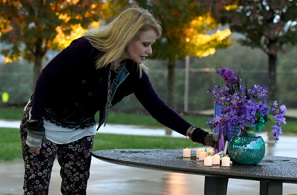 Kayla Hoffman Pekarek, survivor and advocate for survivors of domestic violence and sexual assault, sets up candles and purple flowers prior to a candlelight vigil to bring awareness to those issues on Thursday night at Mercy Park. October is Domestic Violence Awareness month.<br /> Globe | Laurie Sisk