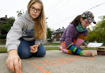 From the left: Volunteers Janelle Gardner and Meghan Moore help promote the band Chased by the Lions with sidewalk chalk at a house on 500 North Moffet on Saturday in preparation for the Second Annual North Heights Neighborhood Porch Fest, which featured 15 musical acts, numerous artists, food trucks and more. Globe | Laurie Sisk