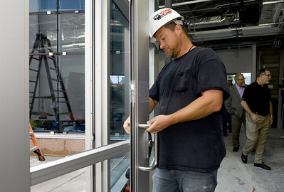 Nathan Mitchell, of Commercial Glass and Metal, installs a handle on a door to the courtyard  of the new Jasper County Juvenile Justice Center as court and county officilas and members of the media tour the building on Wednesday near Sixth and Pearl streets. Globe | Laurie Sisk