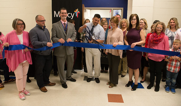 Matt Derfelt, family nurse practitioner at the Mercy Clinic inside Carthage High School, helps cut the ribbon for the clinic on Wednesday afternoon. The clinic, which opened last week, serves Carthage students and staff.<br /> Globe | Roger Nomer