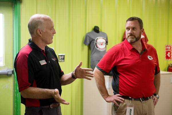 Curt Medlin, sales and marketing with ProPrint, left, talks with Jon Schwarten, chairman of the board of the Joplin Workshops, about the company's new partnership with the workshops announced on Monday.<br /> Globe | Roger Nomer