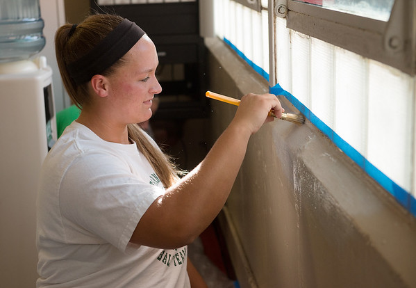 Emily Harris, a Missouri Southern junior from Carthage, joins members of the MSSU softball team in painting the office at Eugene Field Elementary in Webb City on Wednesday. The softball team performs community service throughout the year, and Harris set up this project since she attended the school.<br /> Globe | Roger Nomer