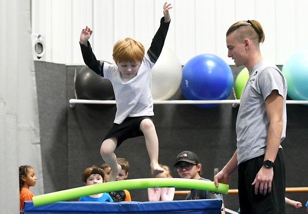 Ninja-in-training Quincey Peters, 4, jumps over a foam bar held by instructor Spencer Cornett during Ninja class on Wednesday night at Ovation Dance Studio in Carthage. The class offers a mix of tumbling and martial arts aimed at teaching children confidence and focus.<br /> Globe | Laurie Sisk