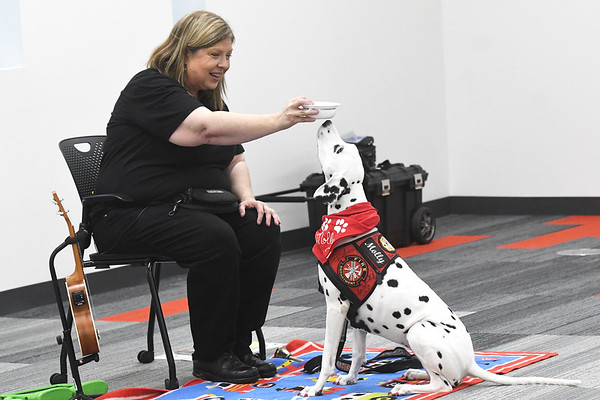 """Molly"" the fire safety dog and owner Dayna Hilton demonstrate how to test a smoke alarm during a visit to the Joplin Public Library on Friday. Hilton, a volunteer firefighter and founder and executive director of the Keep Kids Fire Safe Foundation, travels throughout the U.S. to share fire safety tips with children.<br /> Globe 