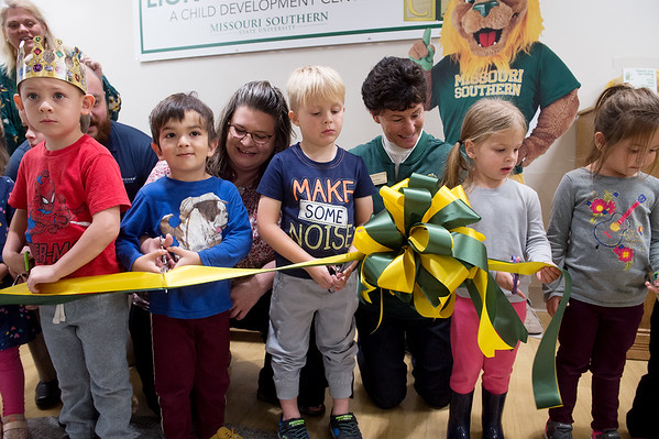 Rikki Smith, member of Leadership Joplin 2018, left, and Anne Sharp, Missouri Southern Foundation Board member, help children at Lion Cub Academy cut a ribbon in celebration of new, all-ability playround equipment at the center on Thursday. Leadership Joplin, Anne Sharp and the Shawnee Tribe of Oklahoma helped donate to the equipment. The ceremony was moved inside due to the weather.<br /> Globe | Roger Nomer