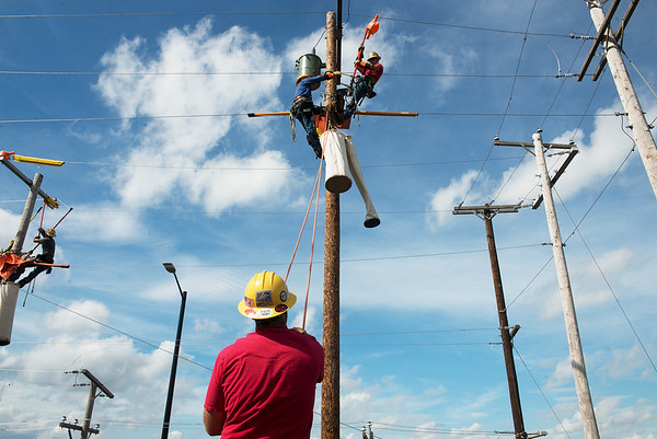 Benjamin Heydt holds ropes for Eric Clark, left, and Aaron Bittle as they train for the Internation Lineman's Rodeo at Liberty Utilities Empire District on Monday.<br /> Globe | Roger Nomer
