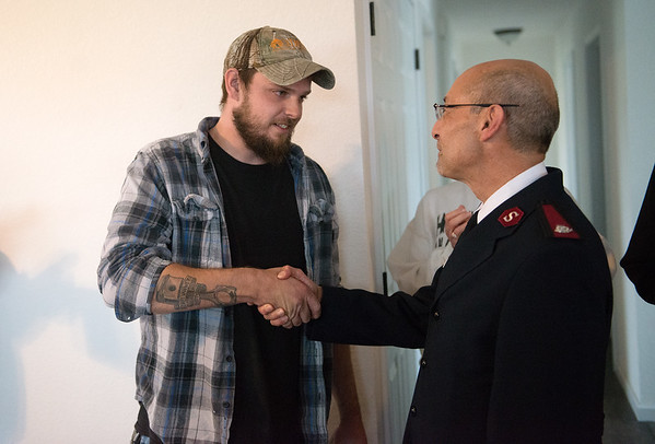 Salvation Army Phillip Aho hands keys to Seth Hurtt for his family's new Habitat home on Wednesday.<br /> Globe   Roger Nomer