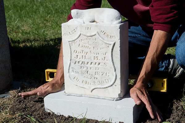 Kevin Wolsey sets a headstone at the Pioneer Cemetery on Thursday in Carthage.<br /> Globe | Roger Nomer