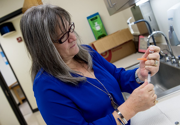 Cynthia Burnham, medical division coordinator for the Joplin Health Department, demonstrates preparing a Hepatitis A vaccine on Monday at the department.<br /> Globe | Roger Nomer