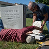 Kevin Wolsey, below, and Billy Joslen, both with Quality Memorial, set a headstone at the Pioneer Cemetery in Carthage on Thursday.<br /> Globe | Roger Nomer