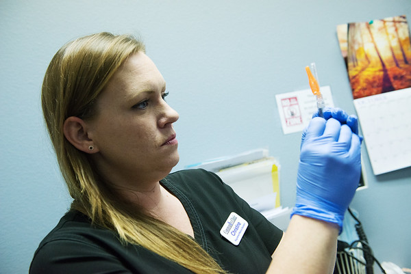 Christine Bright, registered nurse medical assistant at the Joplin Community Clinic, works with a flu shot on Wednesday at the clinic.<br /> Globe | Roger Nomer