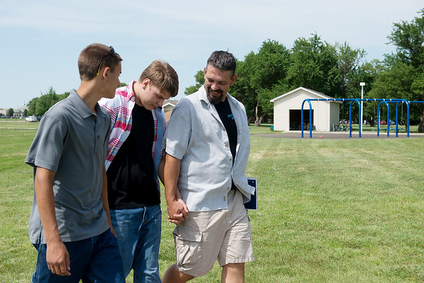 Michael Millman Jr., also known as Little Michael, walks with his brother Lucas and father Michael Sr. during their June 8 visit to Heartspring in Wichita, Kan.<br /> Globe   Roger Nomer