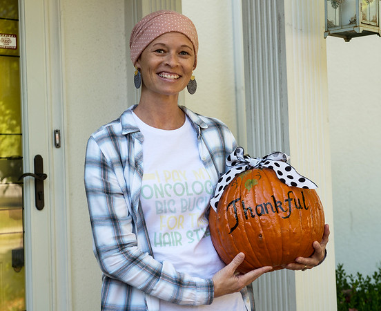 Rachele' Davis holds a pumpkin given to her from a mysterious neighbor that reflects her outlook during her treatment for breast cancer.<br /> Globe | Roger Nomer