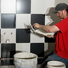 Travis Wescott, with Steve Craig's Floor Covering, works on tile for a restaurant at the Decades of Wheels museum on Tuesday in Baxter Springs.<br /> Globe | Roger Nomer