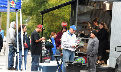 Visitors sample the fare from several food trucks during Porch Fest on Saturday in the North Heights Neighborhood. Globe | Laurie Sisk