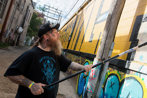 Darryl Becker works on a mural in the alley west of Sixth Street in downtown Joplin on Thursday.<br /> Globe   Roger Nomer