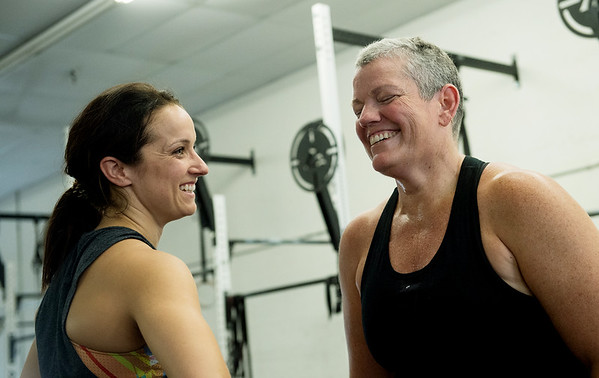 Dani Schmidt, left, talks with Stephanie Miller during a crossfit workout on Tuesday at the Honey Badger Gym.<br /> Globe | Roger Nomer