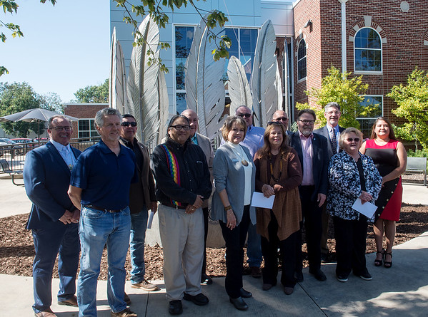 Leaders representing NEO University and 10 area tribes and nations pose for a photo with the Centennial Tribal Monument at NEO on Monday.<br /> Globe | Roger Nomer