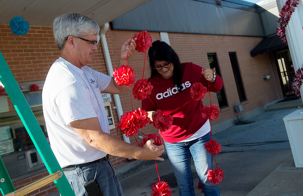 Mark Howard, custodian with Webb City, and Yaqueline Ochoa, accounting clerk, help decorate Webb City Hall for the high school's homecoming parade on Wednesday.<br /> Globe | Roger Nomer