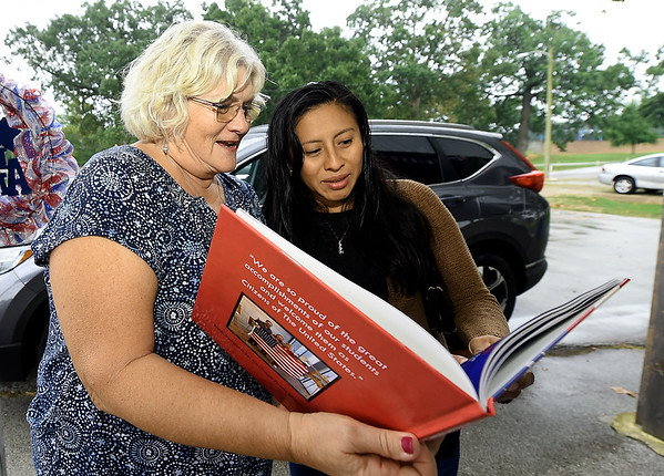 ESL instructor Rhonda Wyrsch and Lillian Hernandez reminisce as they look through a book of photographs of classes and activities of the first three years of the Carthage Public Library Citizenship Class during a reunion on Saturday at Municipal Park.<br /> Globe   Laurie Sisk