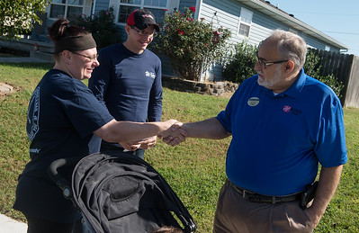 Michael Wiggins, member of the Salvation Army advisory board, right, congratulates Kristen Asbell and Dillon Sprague on their new Habitat home on Monday in Joplin.