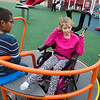 Douglas Smith and Makenzie Gant, third graders, play on an adaptive carousel at the Power of Play playground in Carl Junction on Thursday.<br /> Globe | Roger Nomer