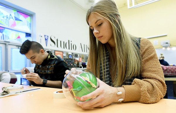 Carthage High School senior Hallie Patrick, right,  works on an ornament comemorating the first World's Fair, which was held in St. Louis, while senior Abraham Figueroa works on a tiny scale of the state capitol building on Tuesday at CHS. The 24 ornaments designed by CHS students will decorate a Christmas tree representing Missouri in the nation's capitol.<br /> Globe | Laurie Sisk